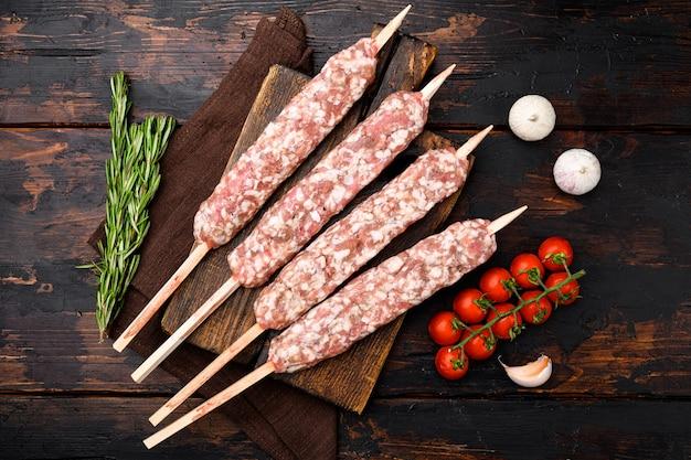 Ensemble de brochettes de shish kebab de mouton cru, avec des ingrédients de gril, sur fond de table en bois foncé ancien, vue de dessus à plat