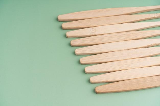 Un ensemble de brosses à dents antibactériennes écologiques en bois de bambou sur fond vert clair. tendances de la protection de l'environnement.