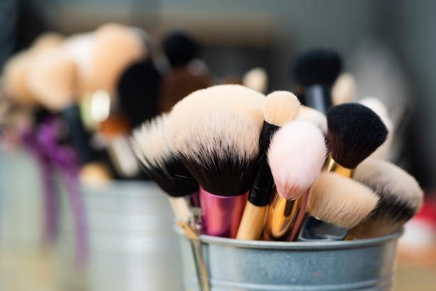 Ensemble de brosses faciales pour maquilleuse ou visagiste. brosses douces naturelles debout dans un pot. gros plan macro photo de pinceaux de maquillage professionnels.