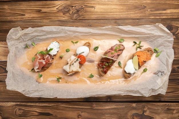 Ensemble de bruschetta avec jambon de parme, boeuf, poitrine de poulet, tomates séchées, fromage mozzarella, saumon, sauce pesto et fromage à la crème