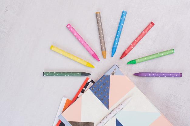 Ensemble de cahiers et crayons colorés sur une surface blanche
