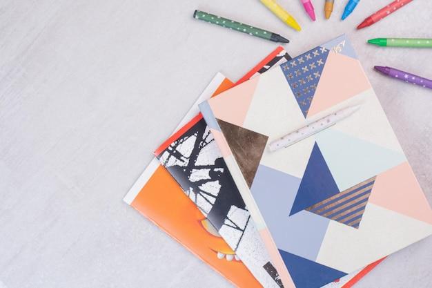 Ensemble de cahiers et de crayons colorés sur une surface blanche.