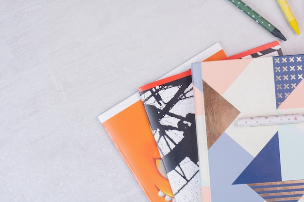 Ensemble de cahiers sur une surface blanche avec un stylo.