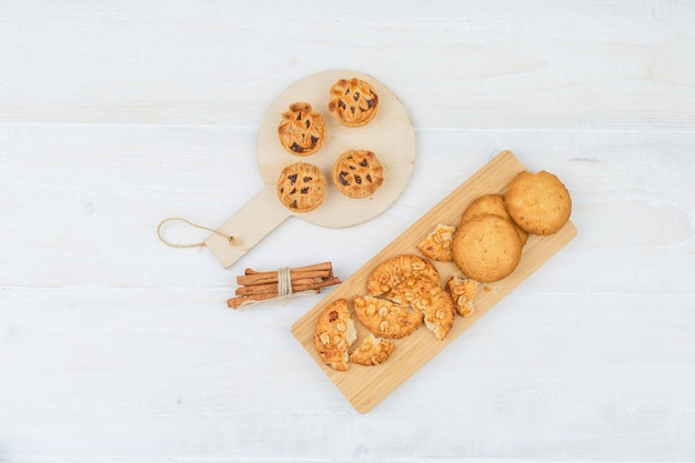 Ensemble de cannelle et différents cookies sur une planche à découper sur une surface blanche