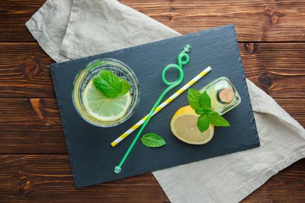 Ensemble de carton noir, pailles, bouteilles de jus et tranches de citron dans un bol sur une surface en bois. vue de dessus.