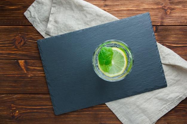 Ensemble de carton noir et de tranches de citron dans un bol sur une surface en bois. vue de dessus. espace libre pour votre texte