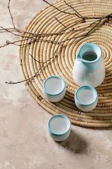 Ensemble en céramique à saké pour boisson alcoolisée japonaise traditionnelle, saké au vin de riz, pichet et trois tasses, debout sur une serviette en paille avec des branches sèches