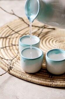 Ensemble en céramique de saké pour boisson alcoolisée japonaise traditionnelle saké de vin de riz versant du pichet dans trois tasses, debout sur une serviette en paille avec des branches sèches