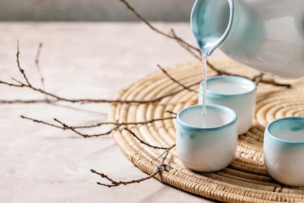 Ensemble en céramique de saké pour boisson alcoolisée japonaise traditionnelle versant du pichet dans trois tasses