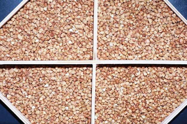 Un ensemble de céréales céréalières. gruau de riz, de sarrasin et de millet dans un plateau en bois. un ensemble de céréales d'épicerie. importation de céréales.