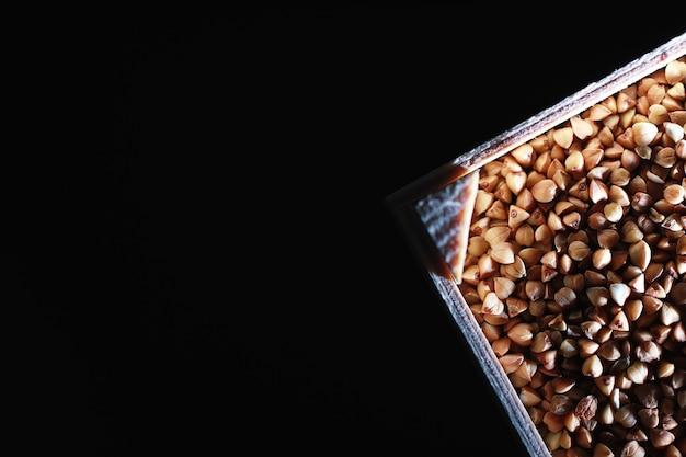 Un ensemble de céréales à grains riz sarrasin et gruau de millet dans un plateau en bois