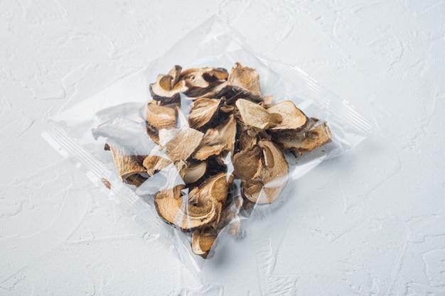 Ensemble de champignons porcini séchés biologiques sauvages, sur fond blanc, en emballage plastique