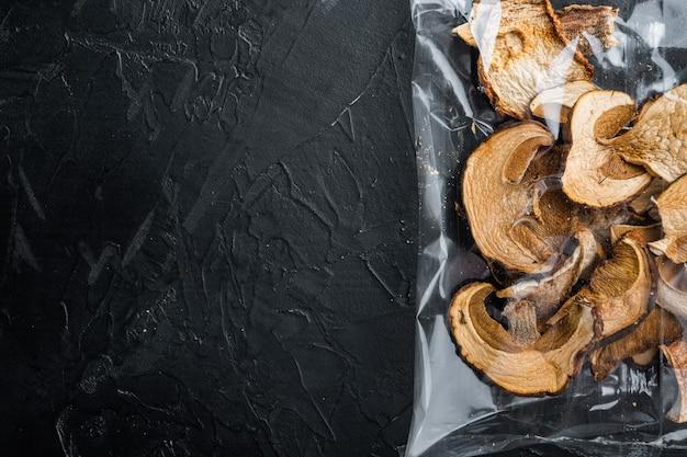 Ensemble de champignons porcini séchés biologiques sauvages, sur fond noir, en emballage plastique, vue de dessus à plat, avec espace pour fond de texte