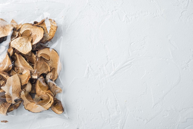 Ensemble de champignons porcini séchés, sur fond blanc, en emballage plastique, vue de dessus à plat