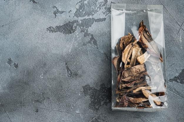 Ensemble de champignons porcini séchés, sur fond gris, en emballage plastique, vue de dessus à plat,