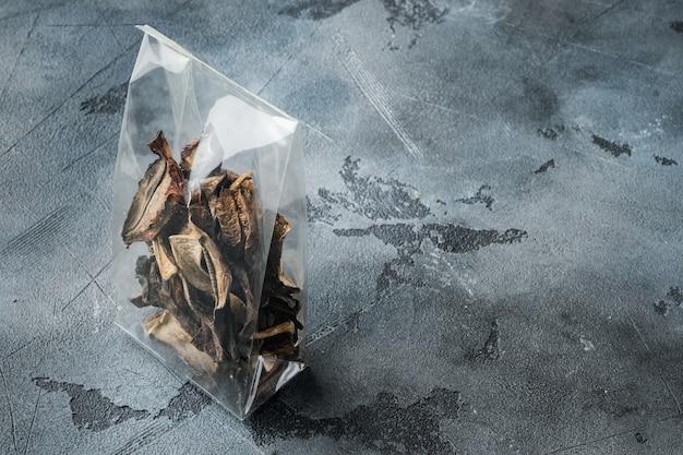 Ensemble de champignons sauvages séchés, sur fond gris, en emballage plastique, avec espace pour fond de texte