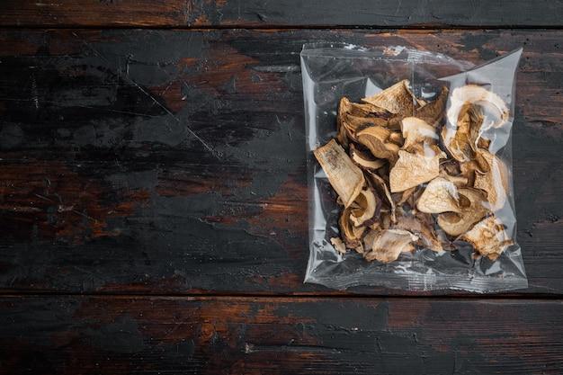 Ensemble de champignons sauvages séchés, sur le vieux fond de table en bois sombre, dans un emballage en plastique, vue de dessus à plat, avec espace pour fond de texte