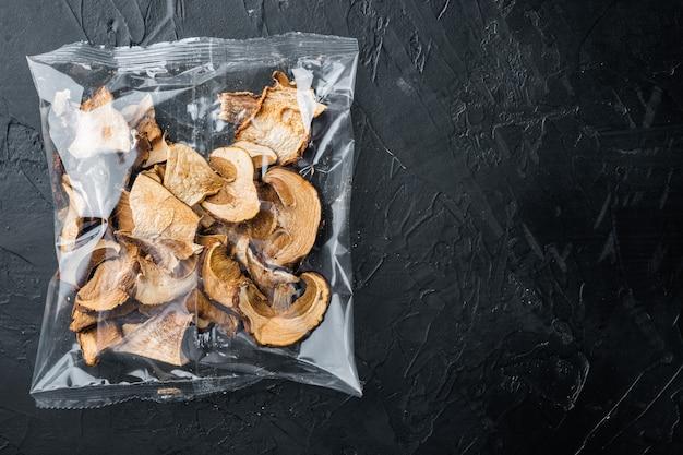 Ensemble de champignons séchés, sur fond noir, en emballage plastique, vue de dessus à plat, avec espace pour copyspace de texte