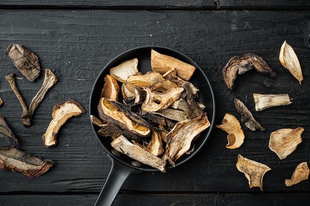 Ensemble de champignons séchés, sur fond de table en bois noir, vue de dessus à plat