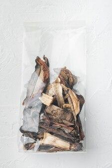 Ensemble de champignons séchés sauvages boletus, sur fond blanc, en emballage plastique, vue de dessus à plat