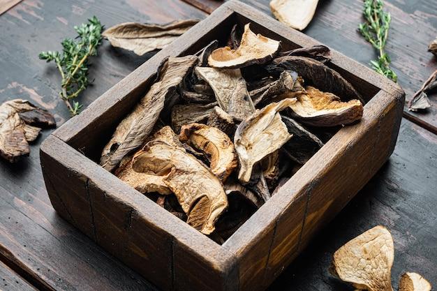Ensemble de champignons séchés sauvages boletus, sur le vieux fond de table en bois foncé