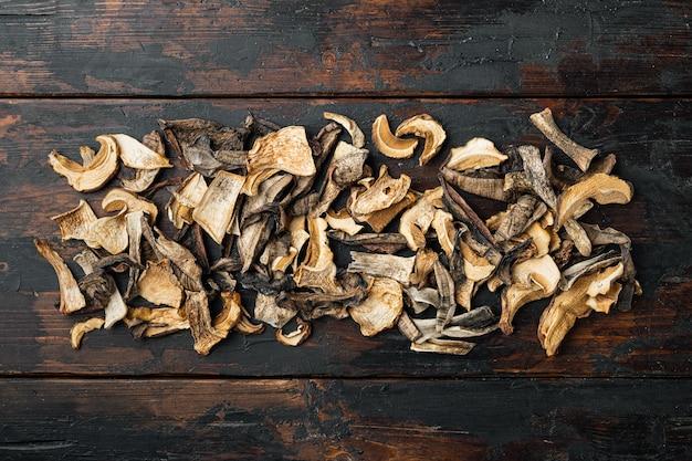 Ensemble de champignons séchés sauvages boletus, sur le vieux fond de table en bois sombre, vue de dessus à plat, avec espace pour fond de texte
