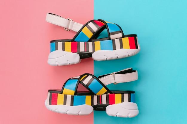 Ensemble de chaussures féminines à la mode. sandales pour femmes multicolores à la mode estivale sur talon haut sur mur bleu et rose. des chaussures élégantes et élégantes pour les filles modernes.