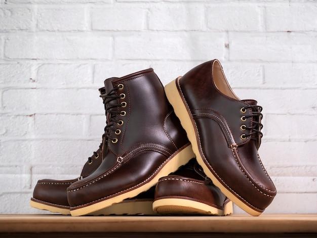 Ensemble de chaussures marron sur le mur de briques blanches