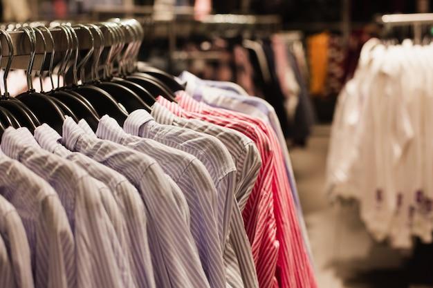 Ensemble de chemises classiques bleues suspendues à un cintre dans une boutique de mode.