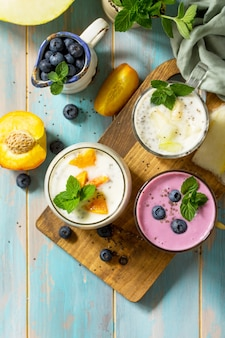 Ensemble de chia sain pudding dans un verre avec myrtille avec melon et pêche vue de dessus à plat