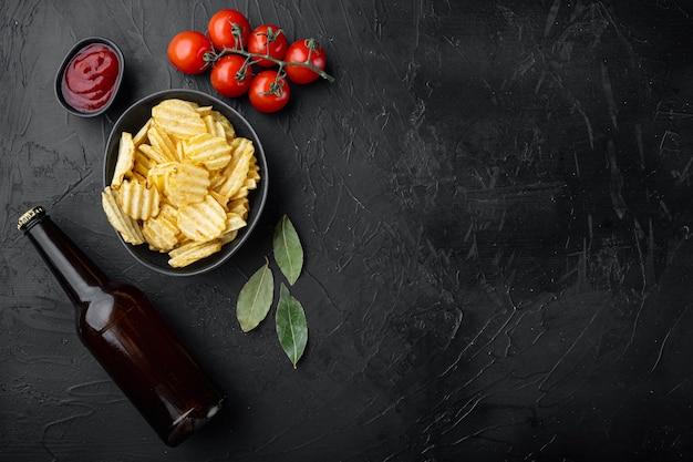 Ensemble de chips de pommes de terre faites maison, avec une bouteille de bière, sur la pierre noire, vue de dessus à plat
