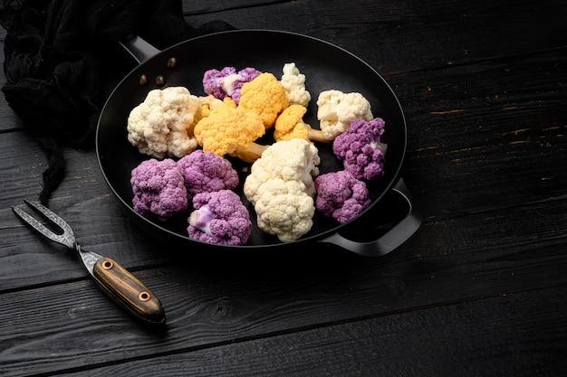 Ensemble de choux-fleurs colorés biologiques, sur poêle en fonte, sur fond de table en bois noir