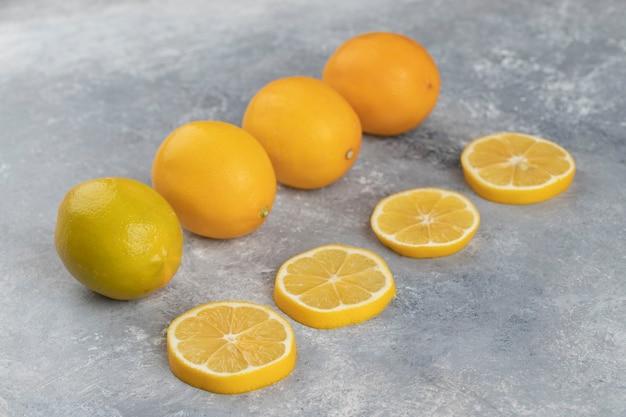 Ensemble de citrons aigres entiers avec des tranches sur un fond de marbre.