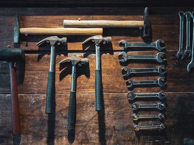 Ensemble de clé et vieux marteaux accrochés au mur en bois, style vertical. de nombreuses tailles de clés et de marteaux sur le mur de planches de bois.