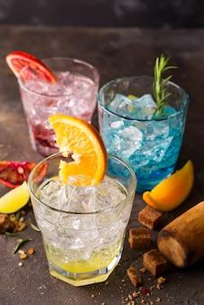 Ensemble de cocktails colorés avec des fruits et des herbes, cassonade sur fond de pierre