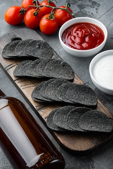 Ensemble de collations croustillantes au fromage et à la ciboulette, avec trempettes de sauces à la crème sure à la tomate et bouteille de bière, sur fond de pierre grise