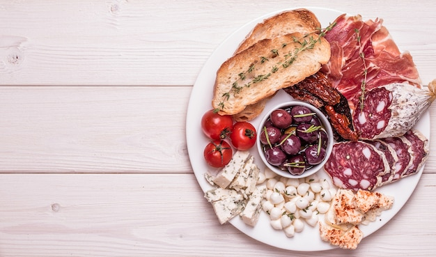 Ensemble de collations. variété de fromage et de viande, olives, tomates sur fond blanc