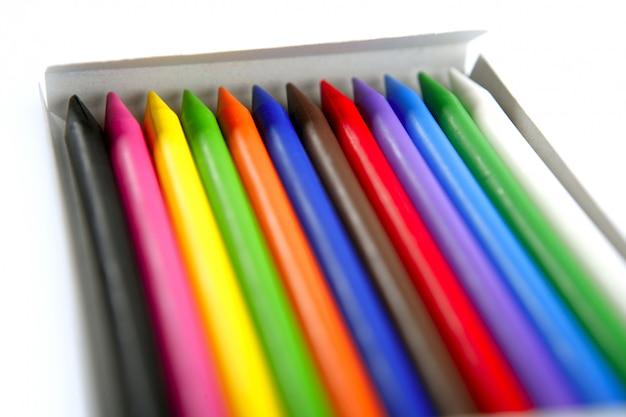 Ensemble coloré de crayon dans une boîte sur blanc