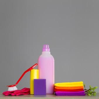 Ensemble coloré d'outils pour nettoyer la maison et les brindilles avec des feuilles vertes sur fond neutre.