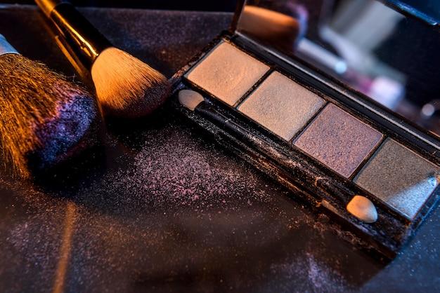 Ensemble coloré pour le maquillage avec des pinceaux sur fond noir