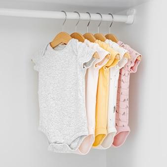 Ensemble de combinaisons bébé pour une fille et un garçon nouveau-nés sur des cintres dans une armoire blanche. maternité, nettoyage de la garde-robe des enfants à la maison. concept de mode minimal.