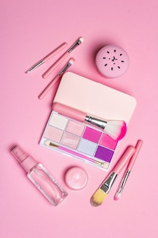 Ensemble cosmétique de maquillage et peignes à cheveux sur rose.
