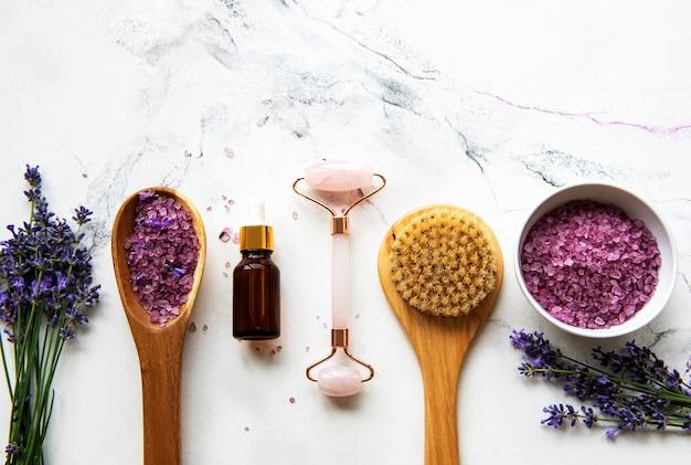 Ensemble de cosmétique spa bio naturel à la lavande. sel de bain à plat, huiles essentielles, rouleau de visage, sur fond de marbre. soins de la peau, concept de traitement de beauté