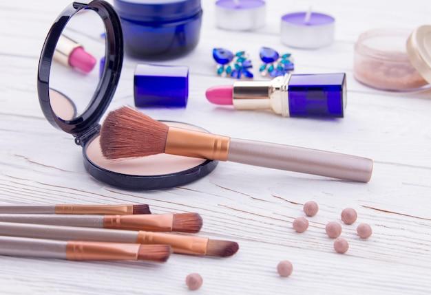 Ensemble de cosmétiques et de bijoux avec des pinceaux à maquillage