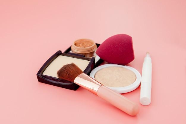 Ensemble de cosmétiques colorés sur fond de table en bois rose, base de maquillage sous forme de coussin. espace copie