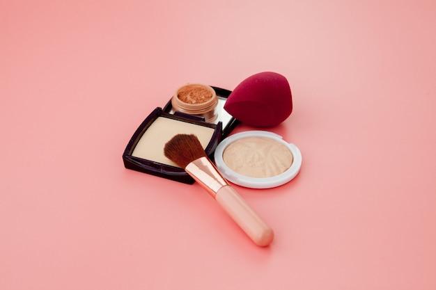Ensemble de cosmétiques colorés sur fond de table en bois rose, base de maquillage sous forme de coussin.