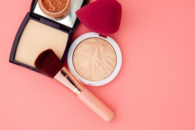 Ensemble de cosmétiques colorés sur rose, base de maquillage sous forme de coussin. espace copie