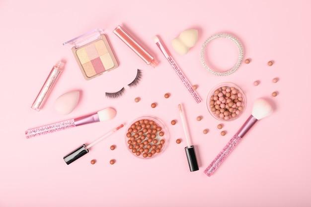 Ensemble de cosmétiques décoratifs et accessoires sur fond rose.