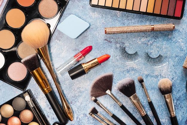 Ensemble de cosmétiques décoratifs, pinceaux de maquillage sur fond bleu. la vue d'en haut