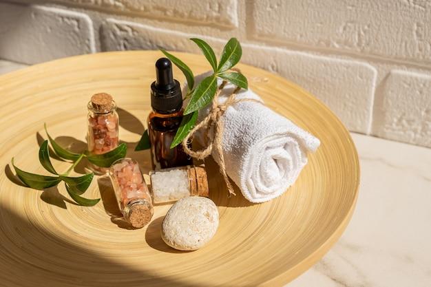 Ensemble de cosmétiques naturels dans un emballage écologique dans une assiette en bambou avec une serviette en coton. spa, produits de beauté pour le bain